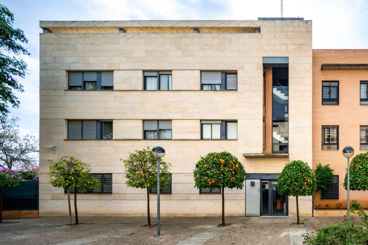 Vista frontal del edificio con los naranjos en la calle
