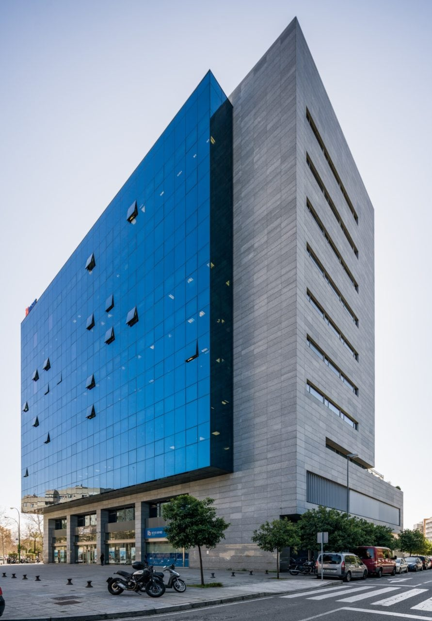 Vista diagonal a pie de calle del edificio y la fachada acristalada