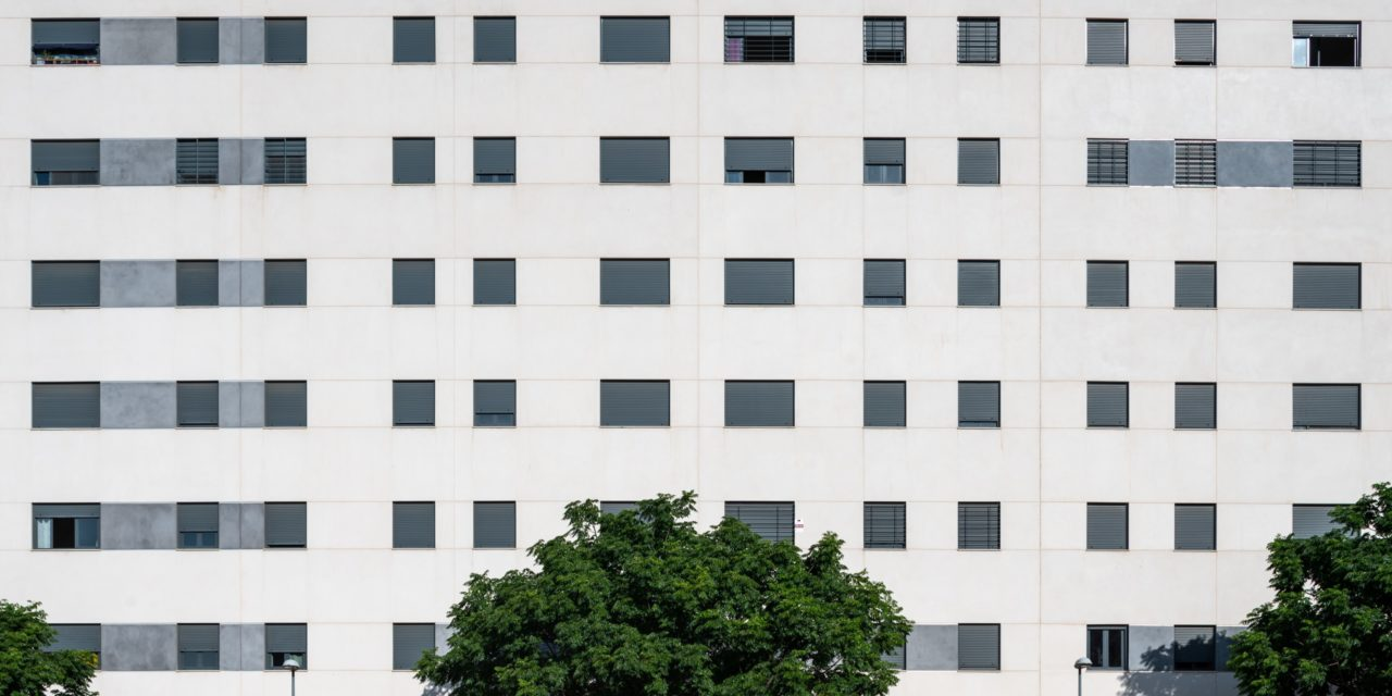 Fachada de gres porcelánico claro con ventanas gris oscuro
