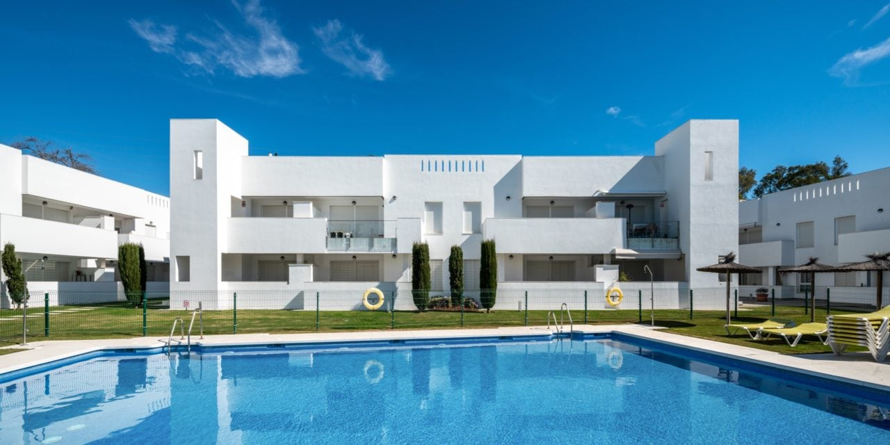 Algunas de las viviendas, con forma sencilla y color blanco, vistas desde la piscina de la urbanización