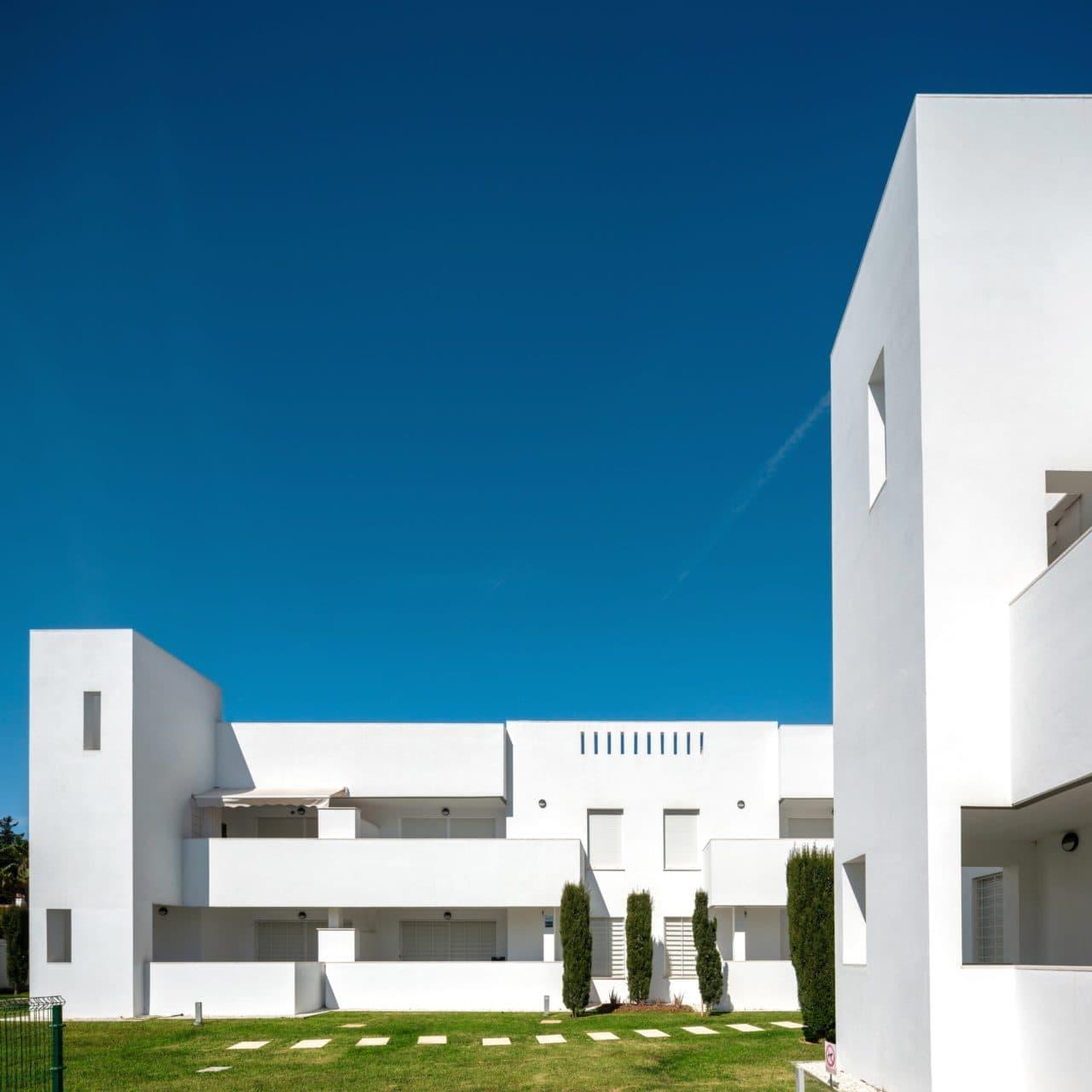 Composición de varias viviendas vistas desde una de las zonas comunes ajardinadas