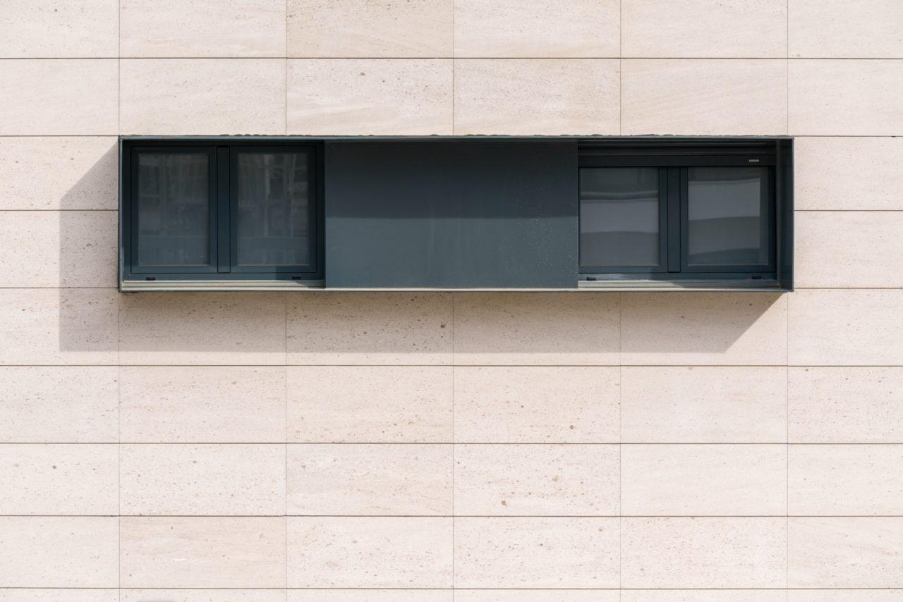 Detalle de ventanas metálicas gris antracita sobre aplacado de piedra Caliza Moca