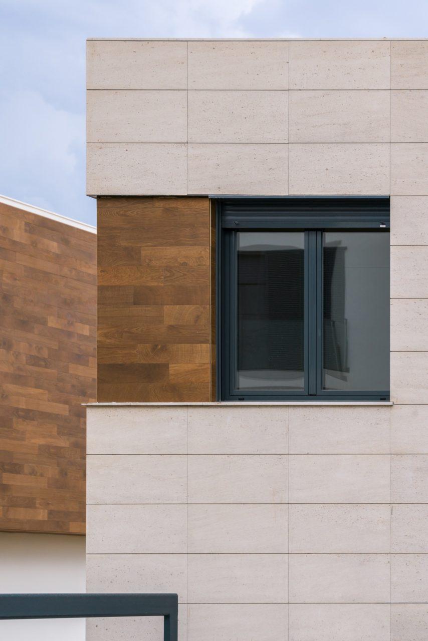 Detalle de una ventana metálica gris sobre aplacado de piedra Caliza Moca