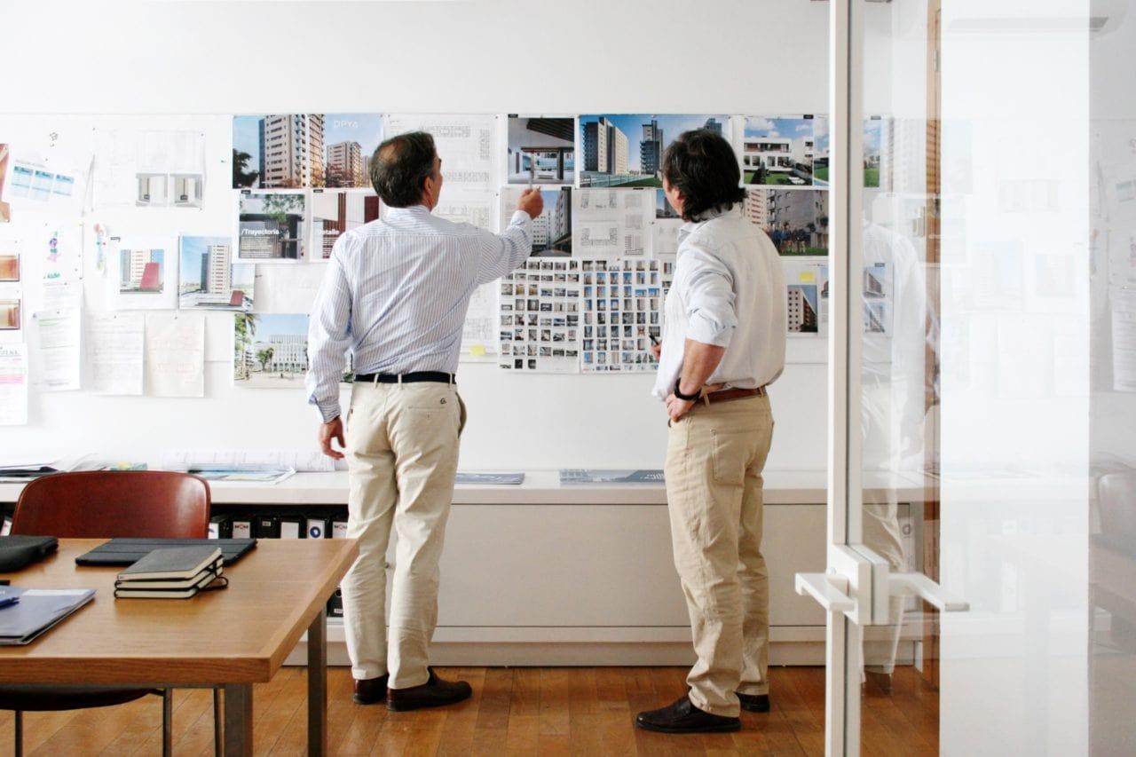 Dos personas trabajando en la oficina sobre varias imágenes pegadas en la pared