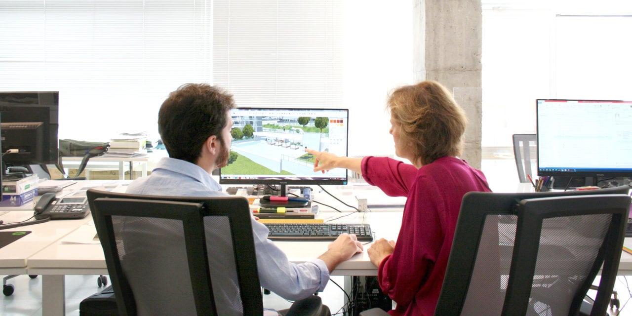 Dos personas trabajando en la oficina con una pantalla de ordenador