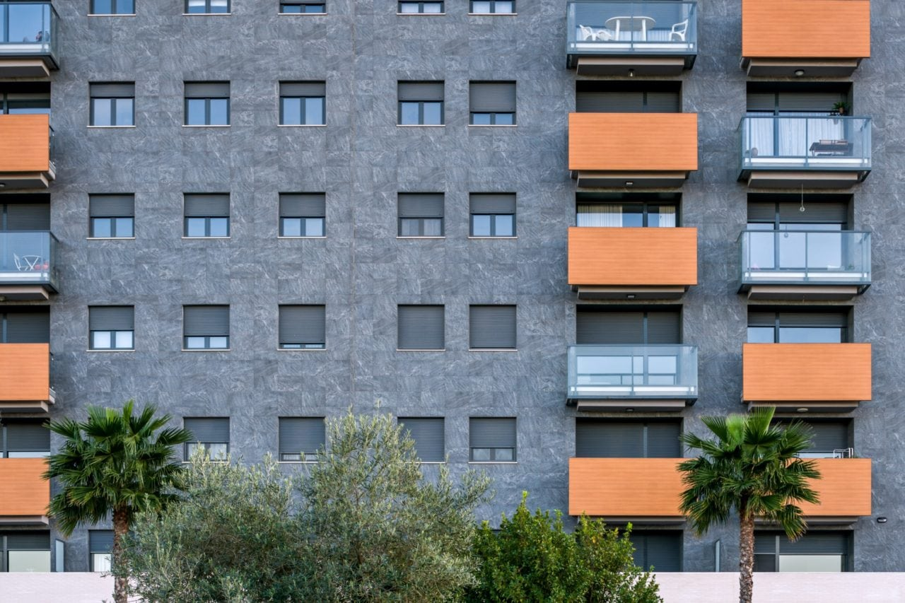 Vista detallada de la fachada gris y los volúmenes generados por las terrazas