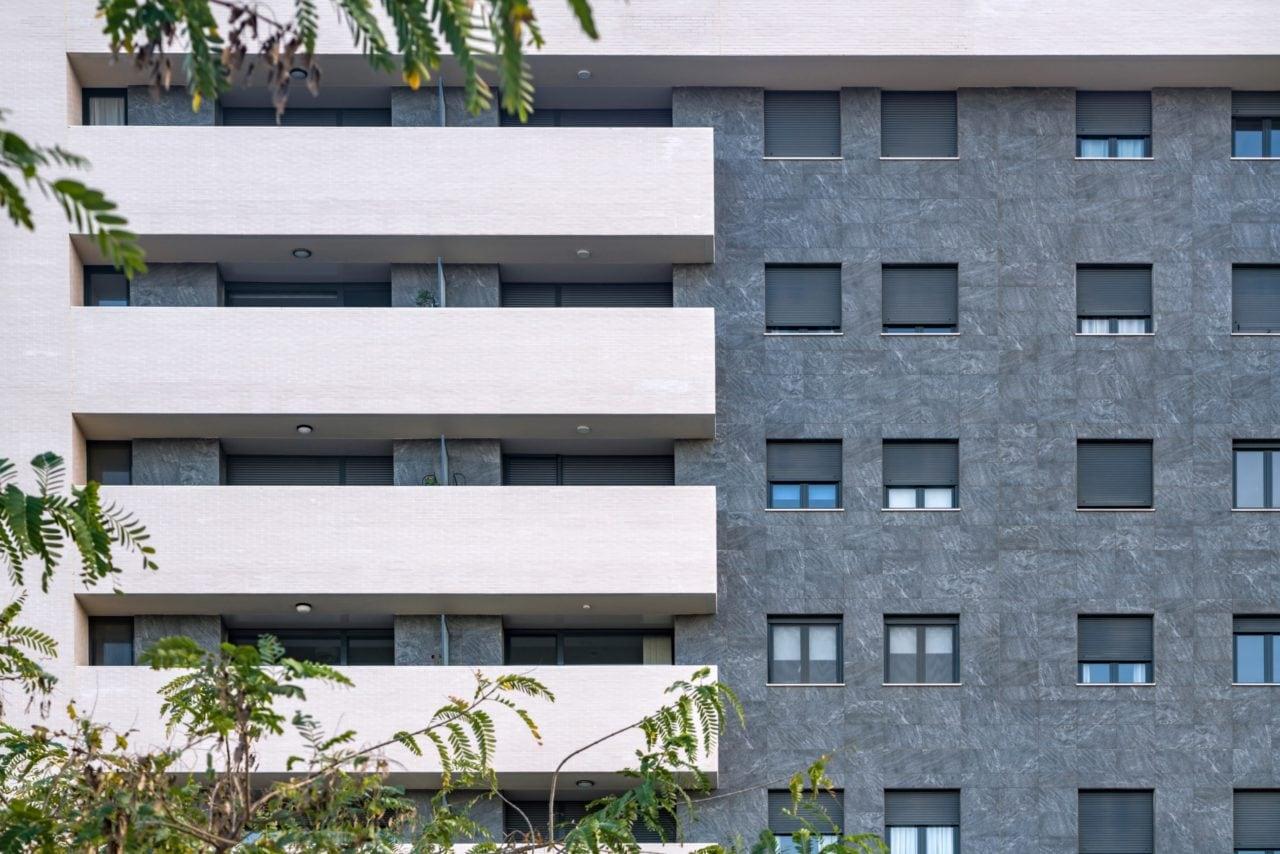 Detalle del contraste de la fachada cerámica gris mate con la banda perimetral de color claro