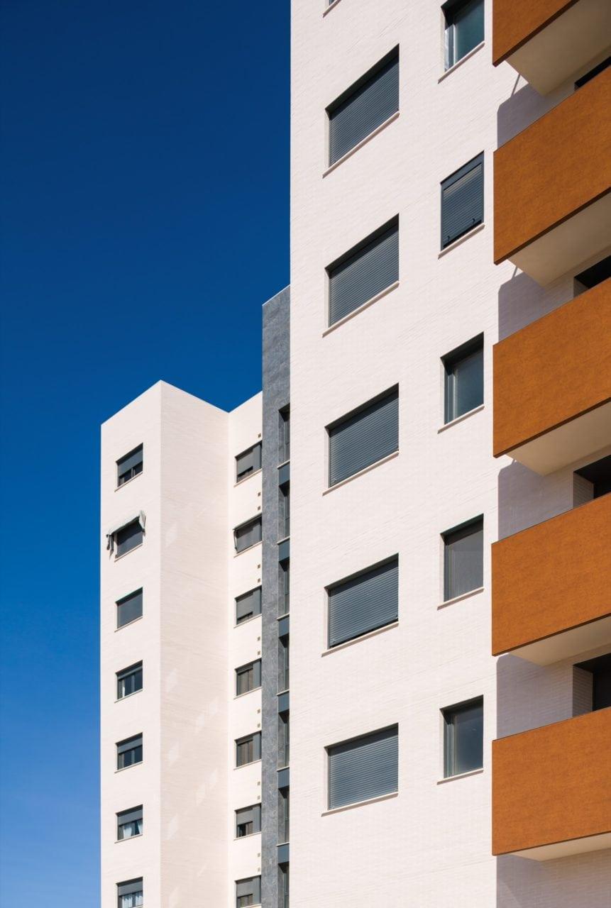Detalle de la fachada en color claro y las terrazas con acabado fenólico